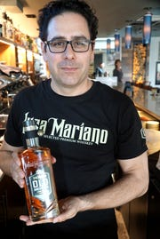 Francesco S. Viola with a bottle of his Luca Mariano Old Americana Bourbon at Plymouth's Cantoro Italian Market on April 10.