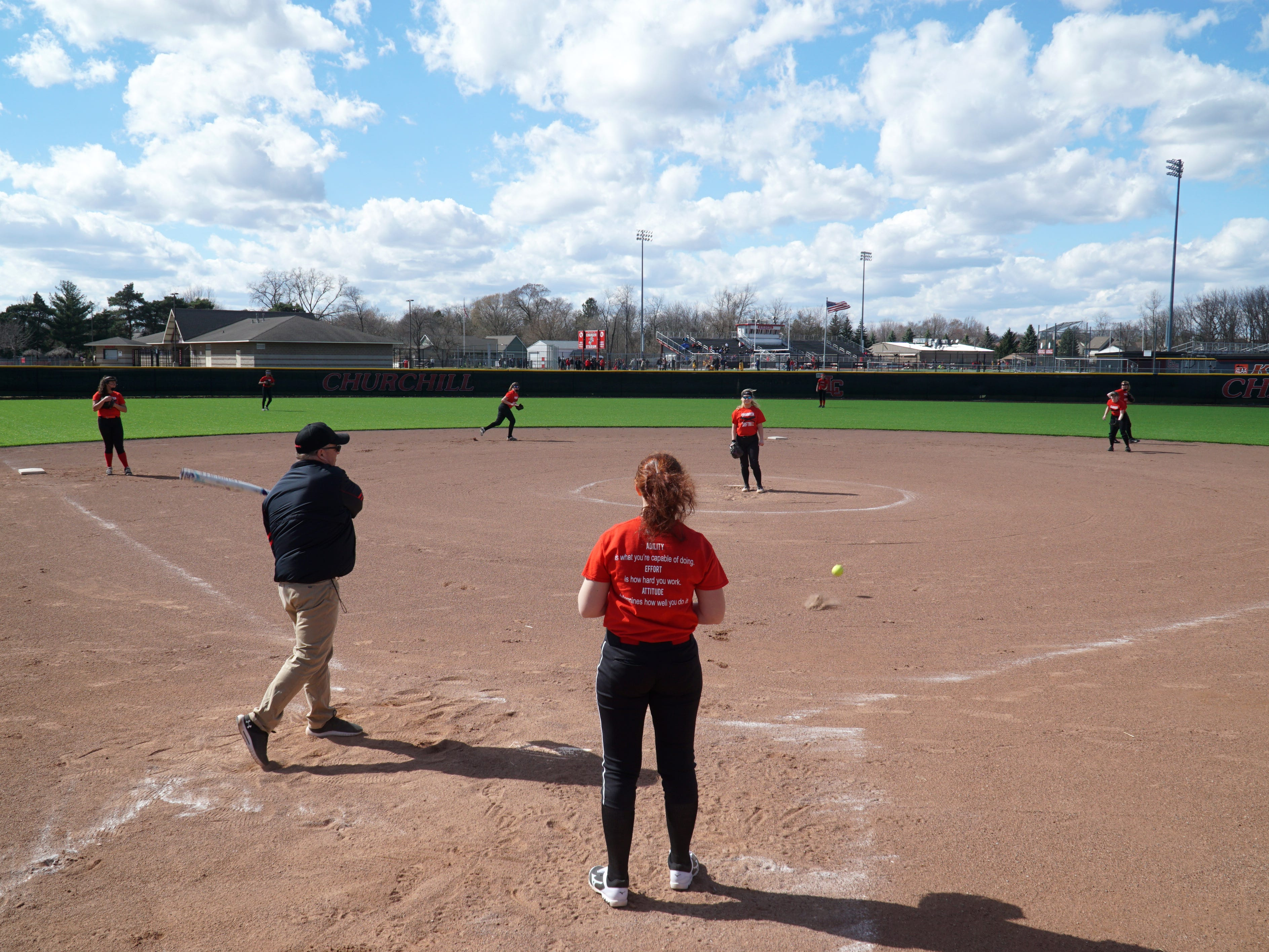 The Livonia Churchill Chargers practice on April 9 as Coach Abe Vinitski hits grounders so they can practice on their fielding.