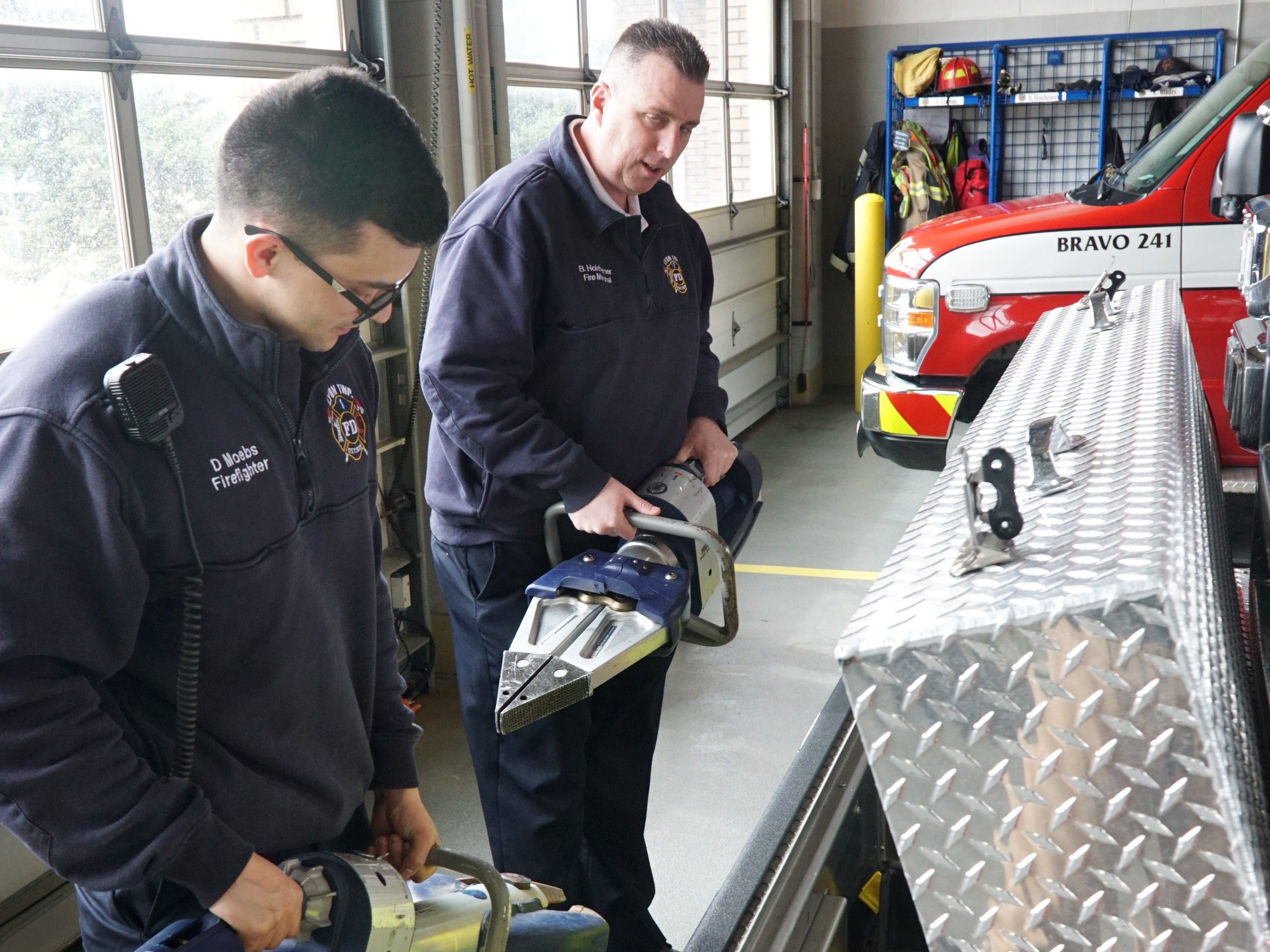 Lyon Township firefighters Doug Moebs, left, and Brian Holzheimer check out their new ladder truck's jaws of life units - which are now battery powered instead of by hydraulics.