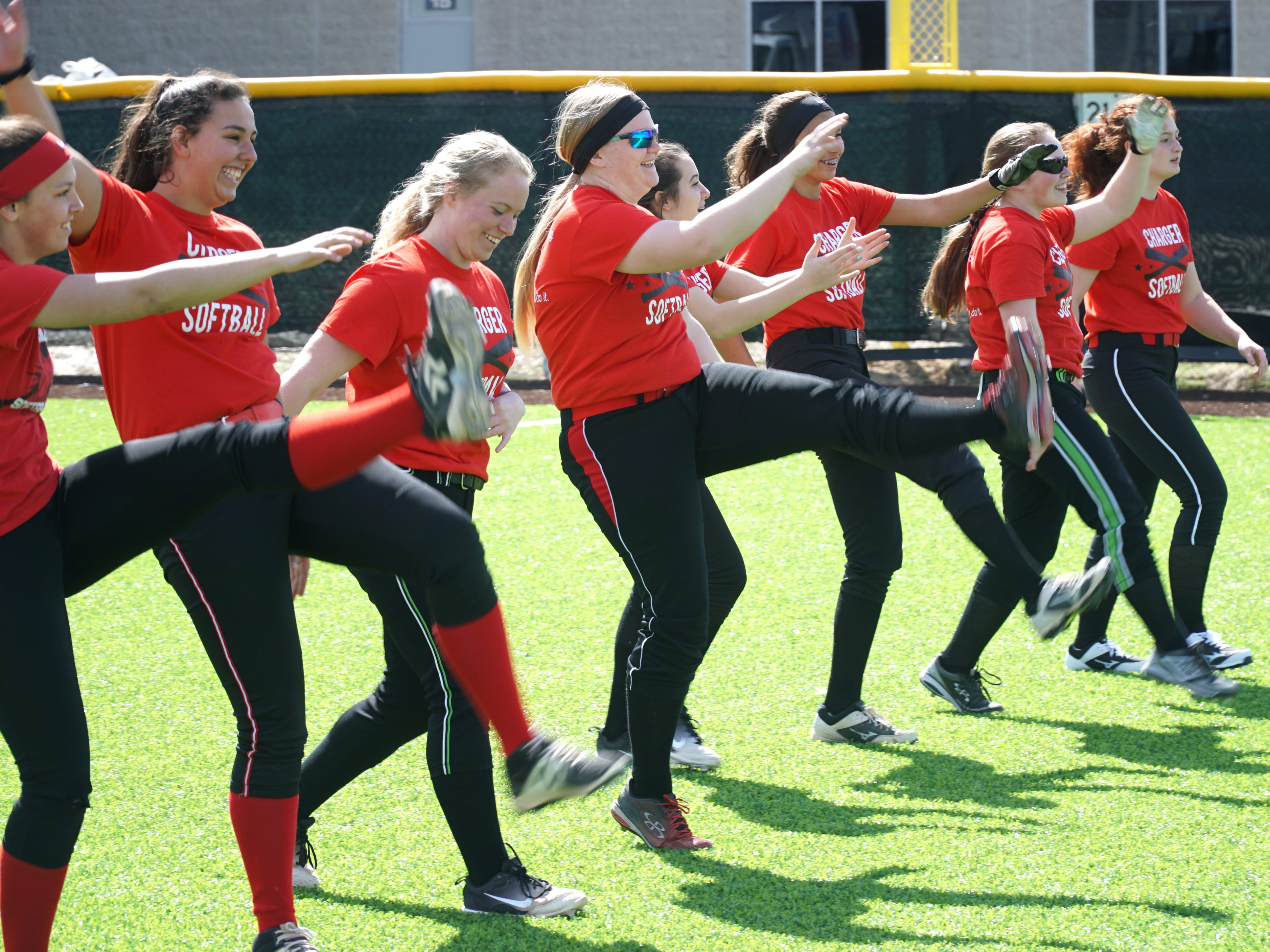 The Livonia Churchill varsity softball team warms up on April 9 at their home field off Newburgh. The team is planing some charity fundraiser games on April 15th and 17th for their coach Abe Vinitski who has severe kidney disease.