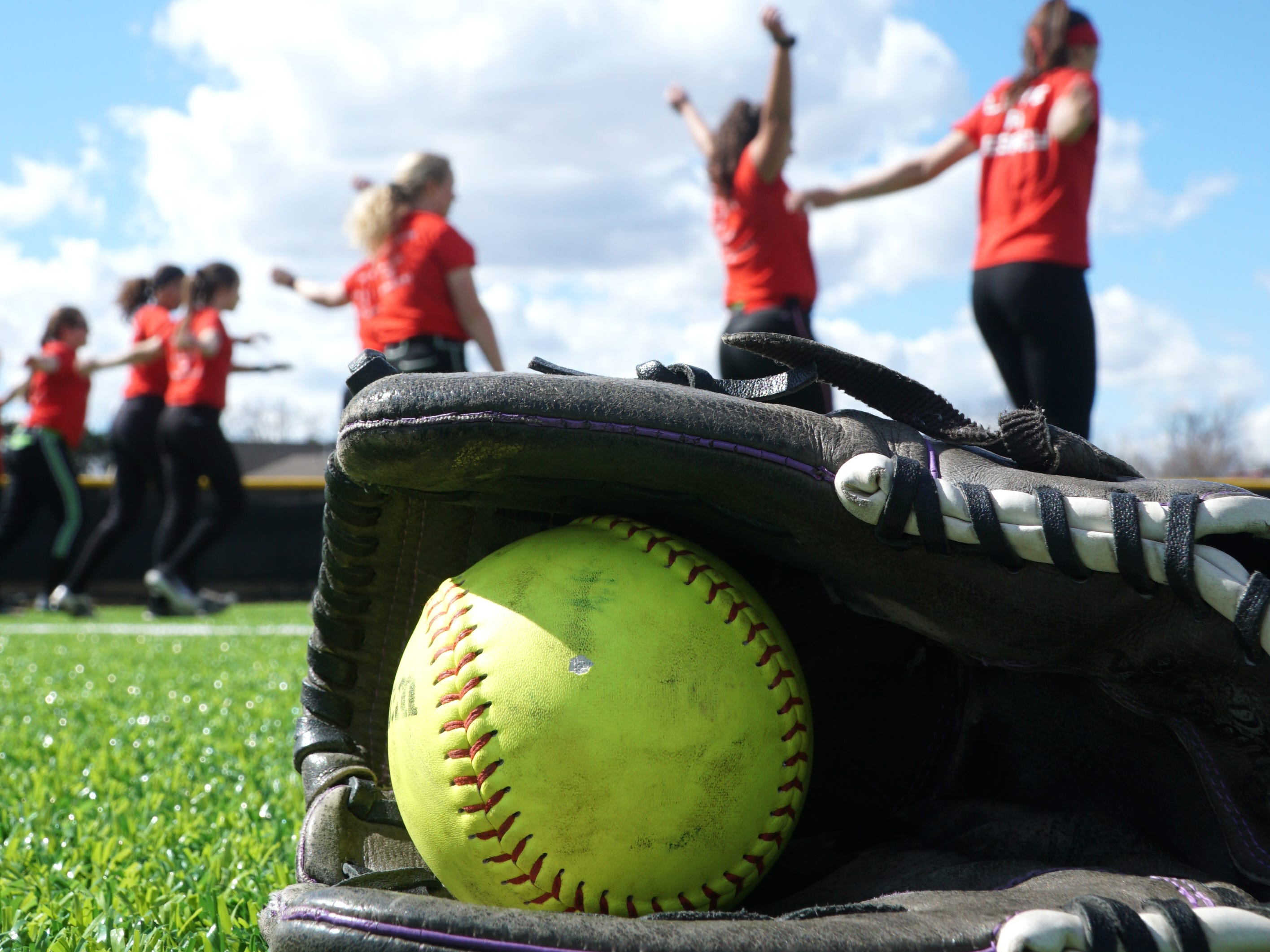 The Livonia Churchill varsity softball team warms up on April  9.
