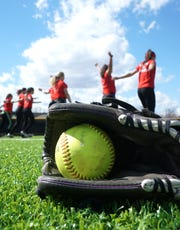 The Livonia Churchill varsity softball team warms up on April  9.