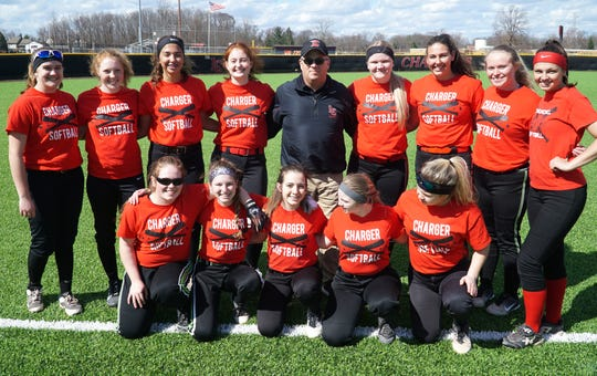 The Livonia Churchill varsity softball team poses with their coach Abe Vinitski on April 9 - before practice. The team will be holding two fundraiser charity games for their coach who has severe kidney disease - on April 15 and 17.