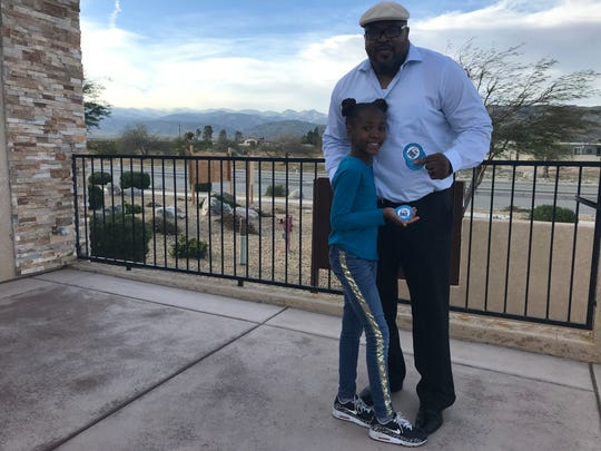 Desert Hot Springs resident Kephyan Sheppard writes articles for Advancing DHS. He and his daughter, Mykayla, hold Advancing DHS bumper stickers on  April 4.