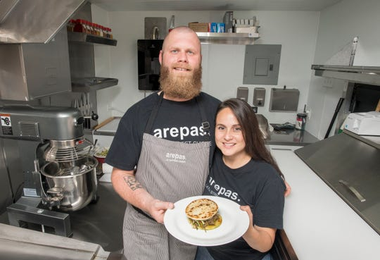 Joshua and Heidi Spiess hold a plated pulled beef arepas in their Arepas food truck in Perdido on Wednesday.