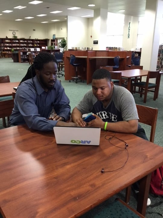Max Petion, a continuous improvement intern at Achieve Escambia, helps a student fill out his Free Application for Federal Student Aid.