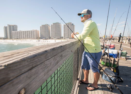 Adam Rasmussen fishes April 10 on the Navarre Beach pier. Rasmussen, who has lived in Navarre for three years, says he would like to see more local control of tax dollars.