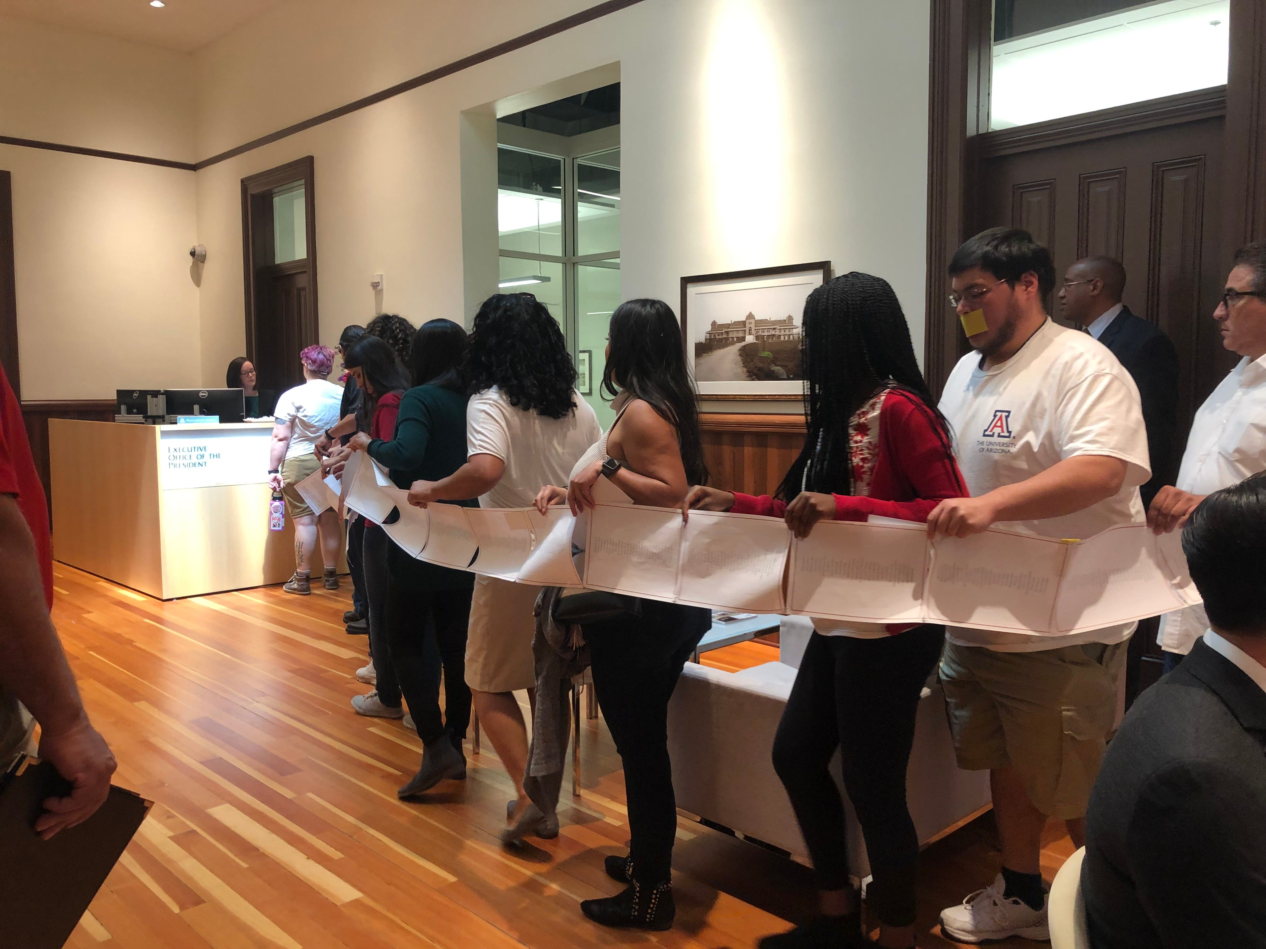 University of Arizona students and faculty deliver a letter to UA President Robert Robbins' office on April 10, 2019.