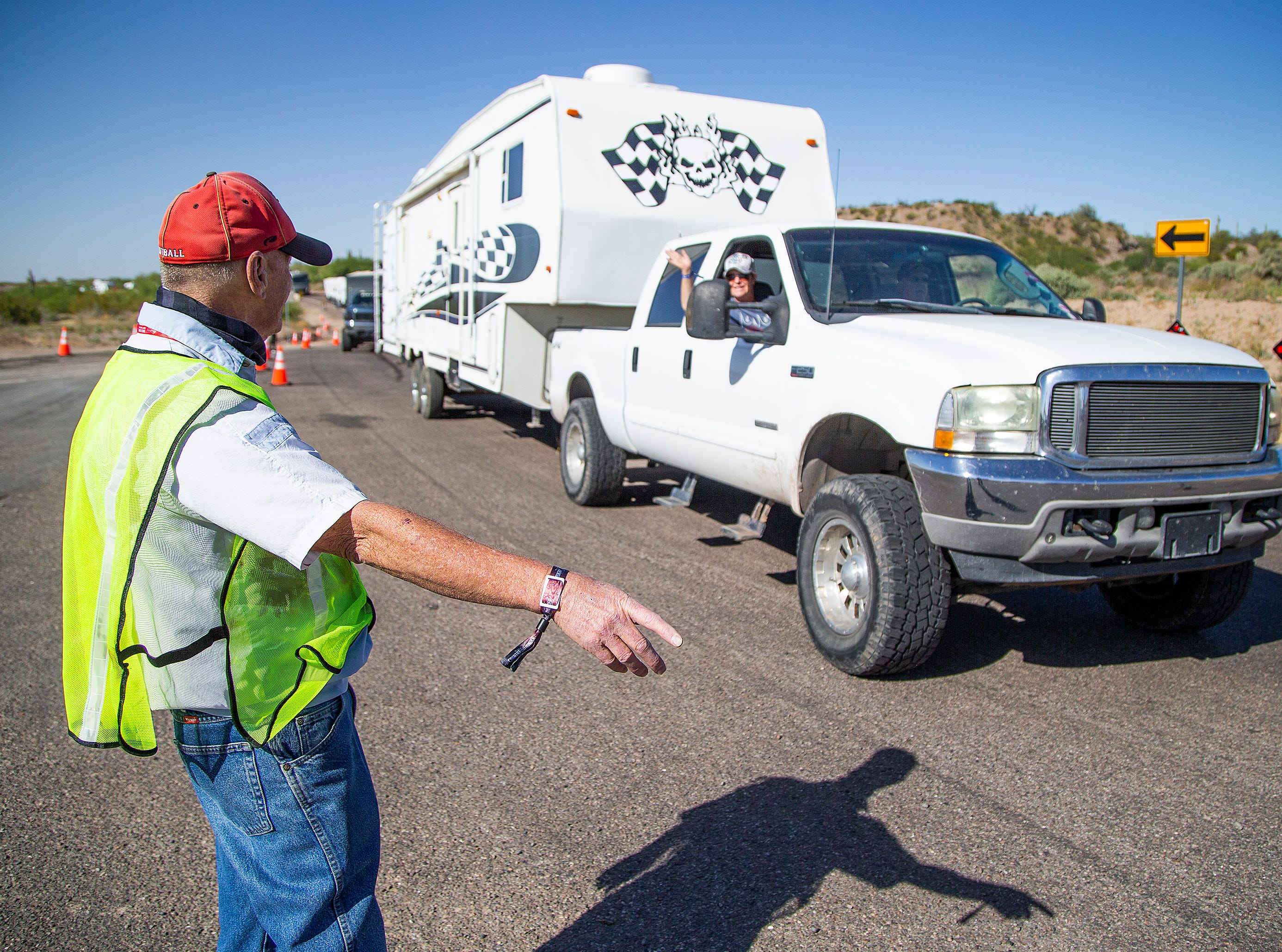 Traffic guide Jack Vaughn directs hundreds of vehicles, including campers and trailers, entering the Country Thunder Arizona 2019 music festival April 10, 2019.