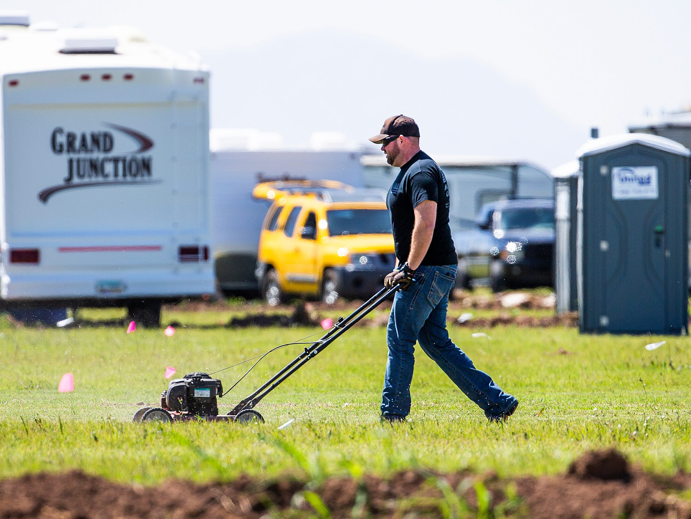 Chuck Law, 35, of Tucson, mows his camping spot at the Country Thunder Arizona 2019 music festival outside Florence April 10, 2019.