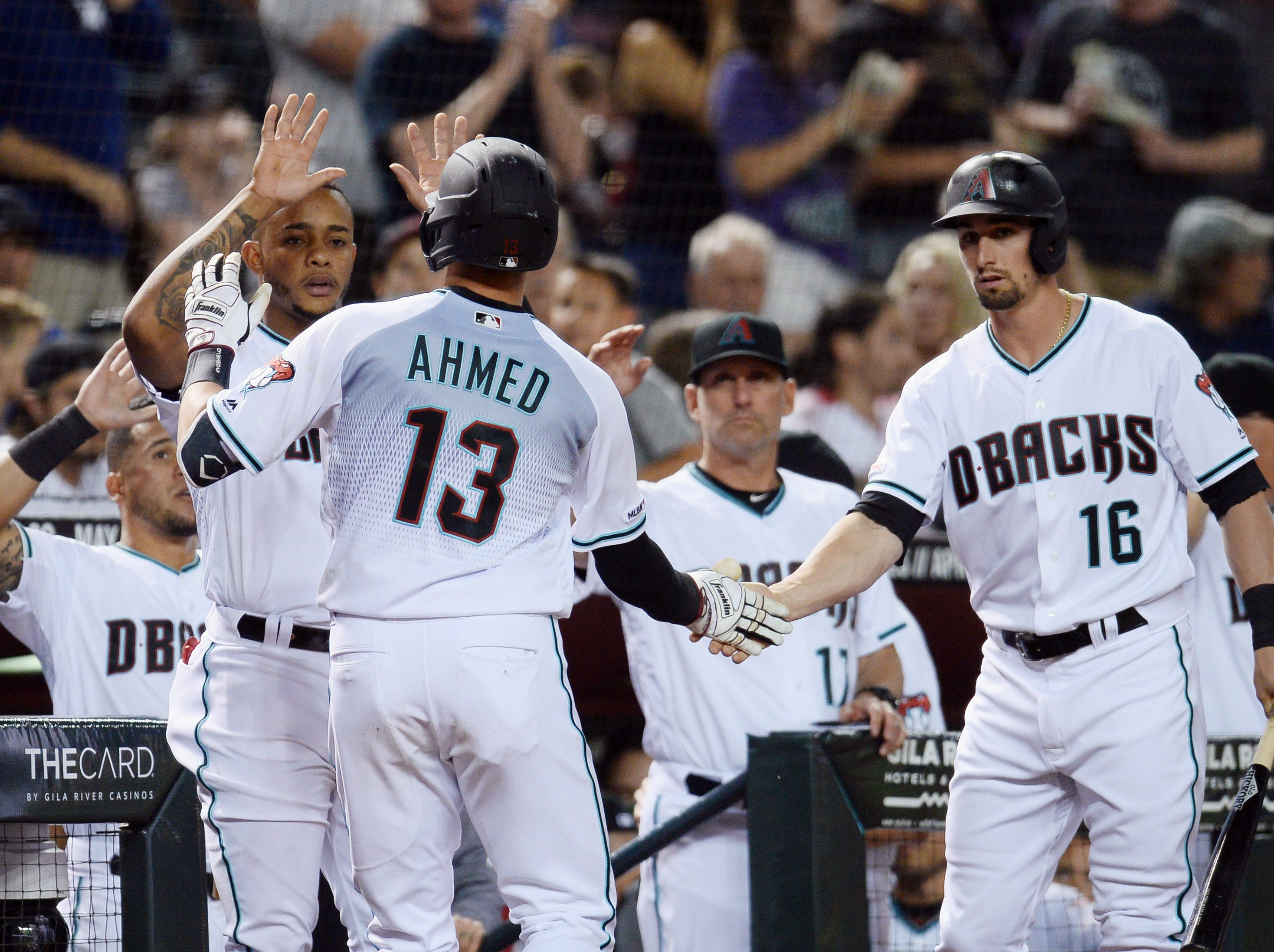 Apr 9, 2019; Phoenix, AZ, USA; Arizona Diamondbacks shortstop Nick Ahmed (13) slaps hands with shortstop Ketel Marte (4) and center fielder Tim Locastro (16) after hitting a solo home run against the Texas Rangers during the seventh inning at Chase Field. Mandatory Credit: Joe Camporeale-USA TODAY Sports