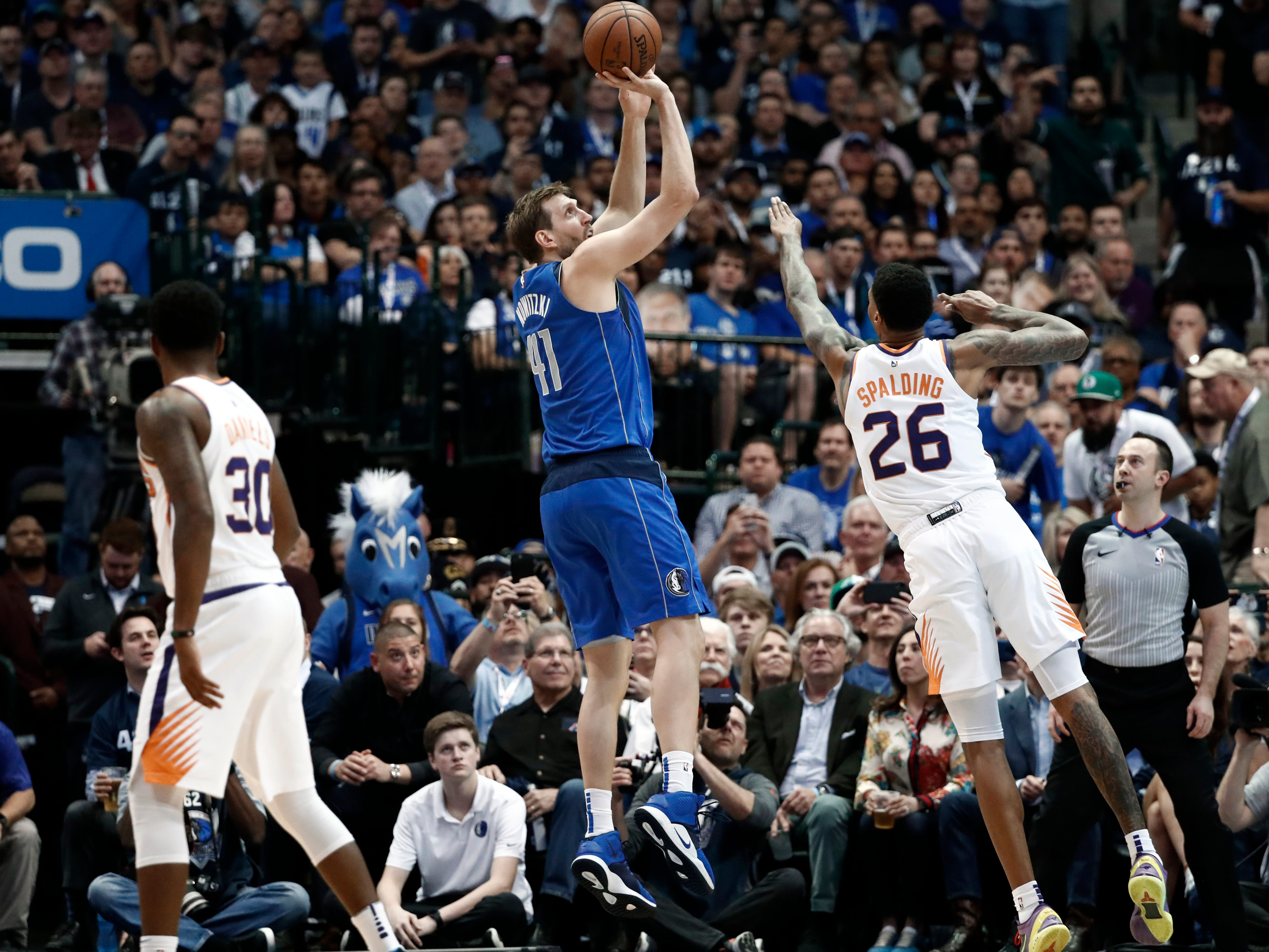Phoenix Suns' Troy Daniels (30) watches as forward Ray Spalding (26) defends against a shot by Dallas Mavericks' Dirk Nowitzki (41) during the first half of an NBA basketball game in Dallas, Tuesday, April 9, 2019. (AP Photo/Tony Gutierrez)