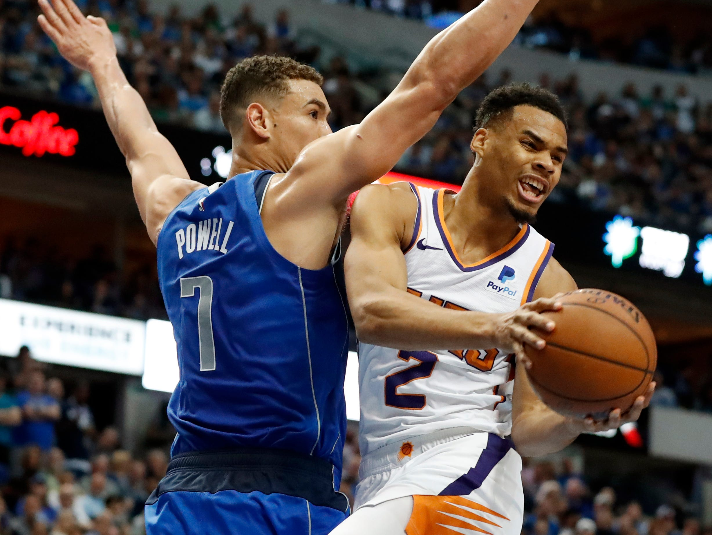 Dallas Mavericks' Dwight Powell (7) turns Phoenix Suns guard Elie Okobo (2) away on a shot attempt during the first half of an NBA basketball game in Dallas, Tuesday, April 9, 2019. (AP Photo/Tony Gutierrez)
