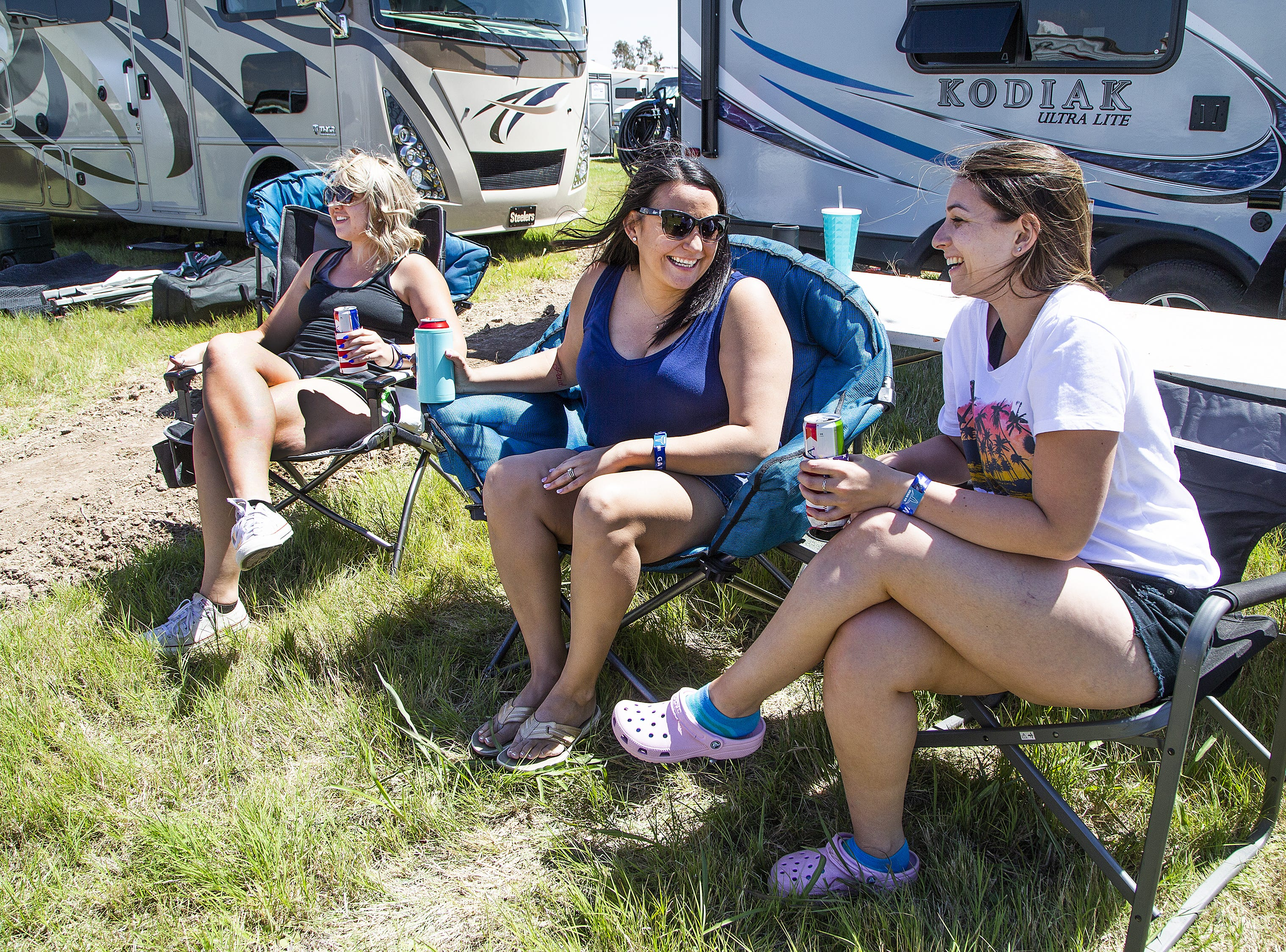 Friends enjoy a cold beer after setting up their camping site at the Country Thunder Arizona 2019 music festival outside Florence, April 10, 2019. From left to right are;  Savannah Ulrick, 24, of Gilbert, Brittany Rhoades, 33, of Chandler, and Katie Carlevaris, 23, from Half Moon Bay, California.