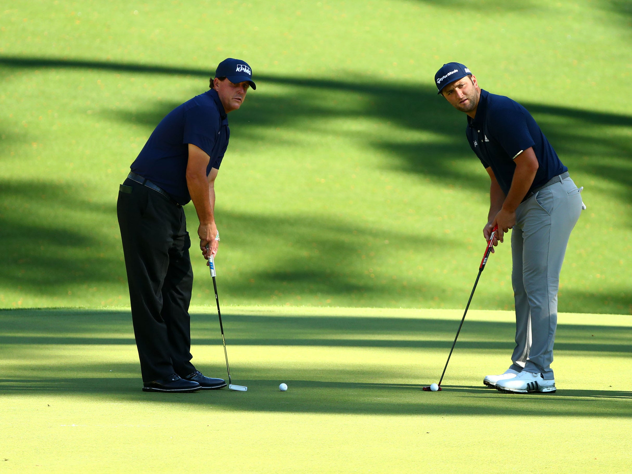 Apr 10, 2019; Augusta, GA, USA; Masters champion Phil Mickelson and Jon Rahm of Spain putt on the 10th green during a practice round for The Masters golf tournament at Augusta National Golf Club. Mandatory Credit: Rob Schumacher-USA TODAY Sports