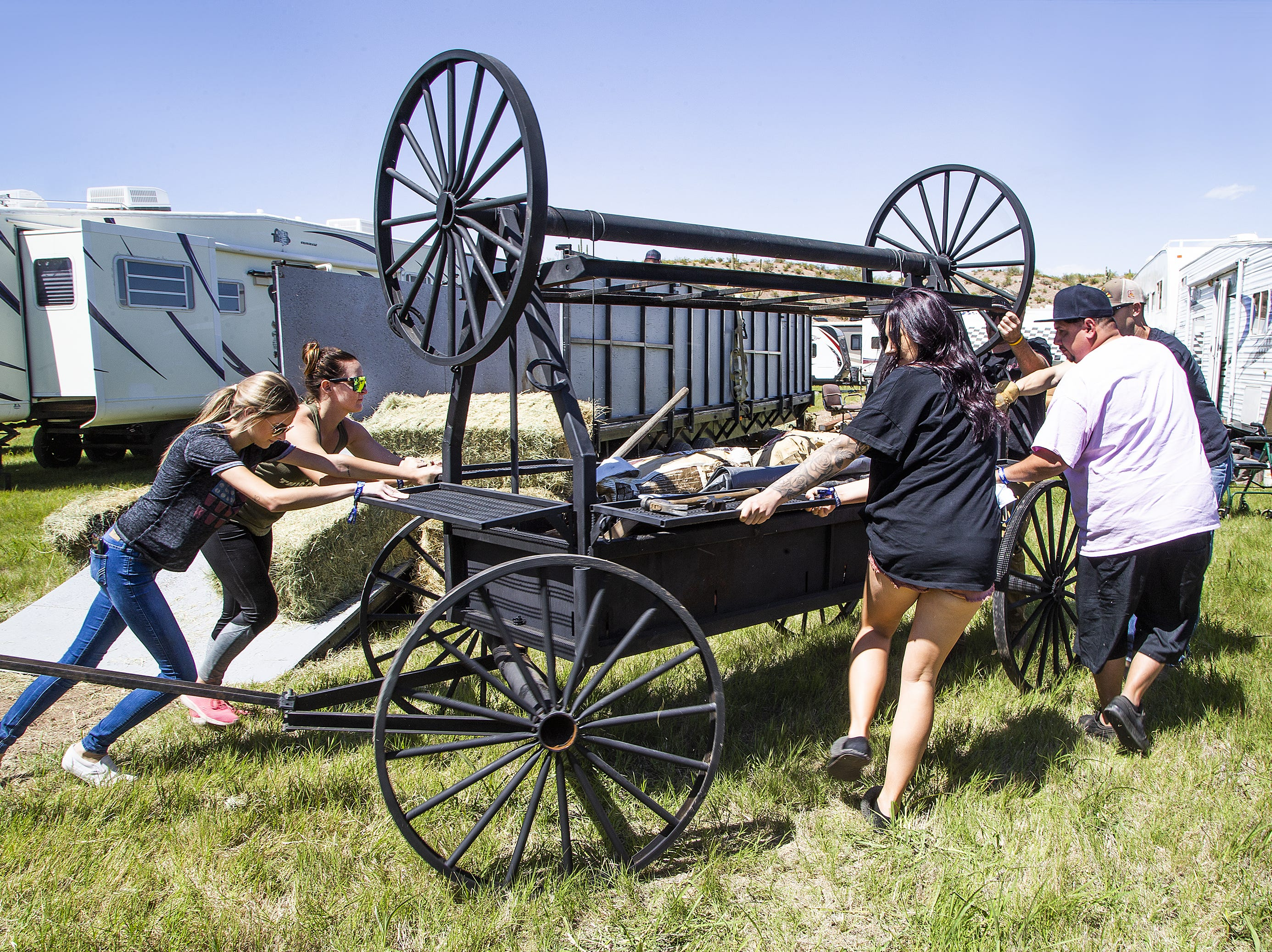 A group pushes a rolling barbecue into a campsite at the Country Thunder Arizona 2019 music festival outside Florence, Wednesday morning, April 10, 2019.