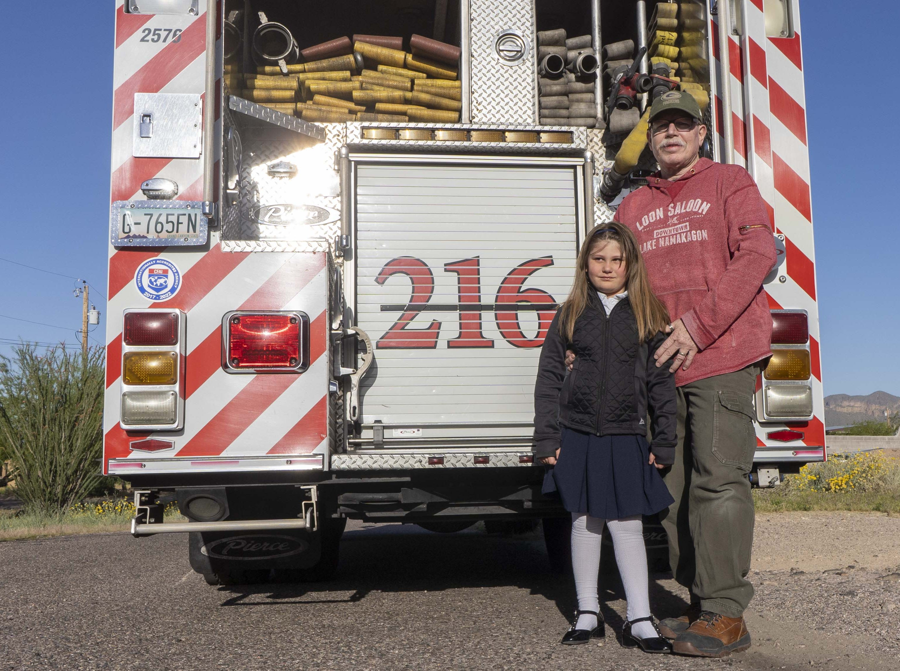 Portrait of Tim Sullivan with his 6-year-old Abi riding in a fire engine #216. Abi is the daughter of Nikki Sullivan, who medically retired in 2015 due to occupational cancer and died last Wednesday. The fire crew will drive Abi, Tim (Nikki's husband and retired fire captain) to the school.