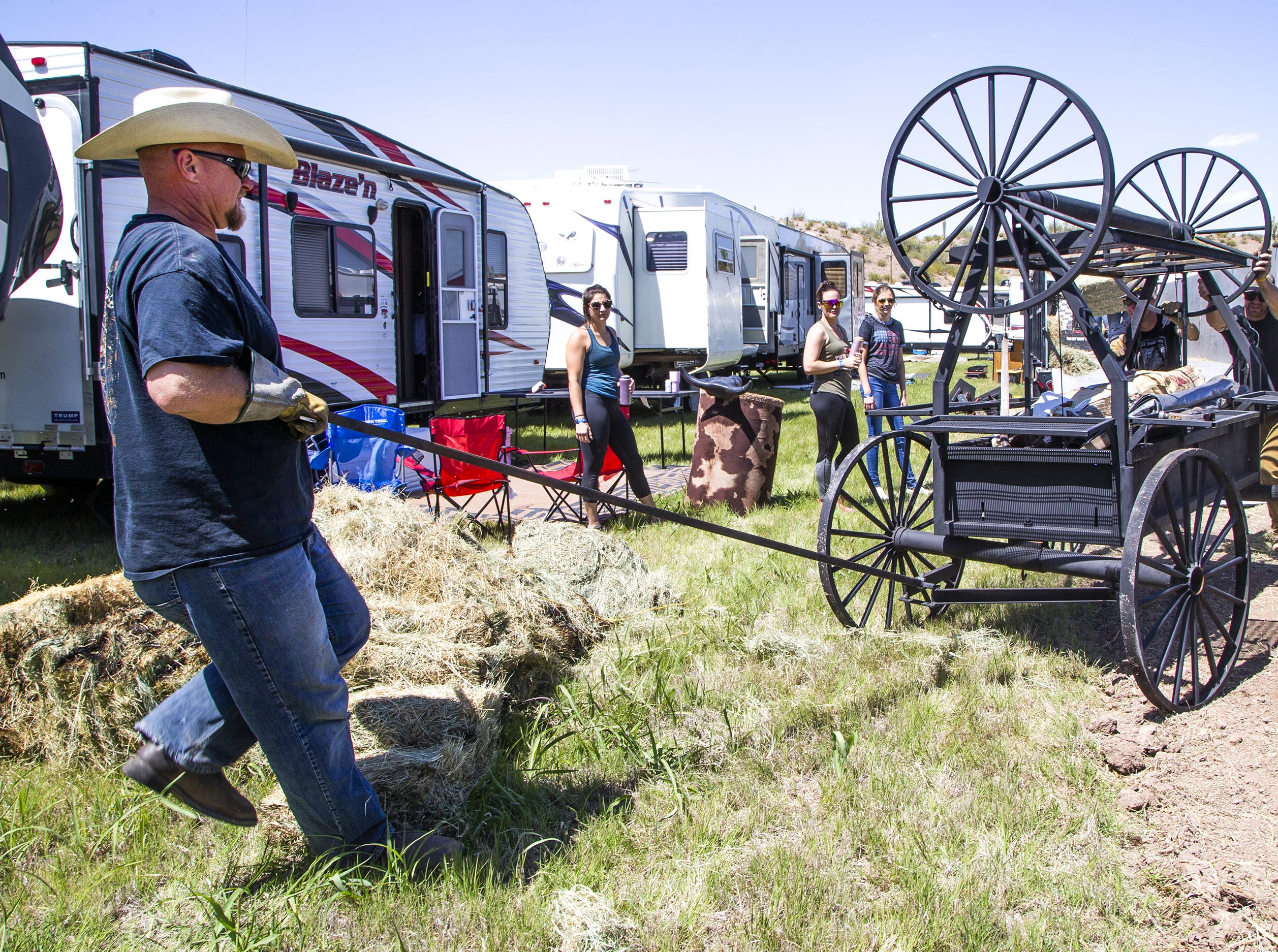 Chris Buhr, left, of Maricopa, pulls his rolling barbecue off a trailer into a campsite at the Country Thunder Arizona 2019 music festival outside Florence, April 10, 2019.