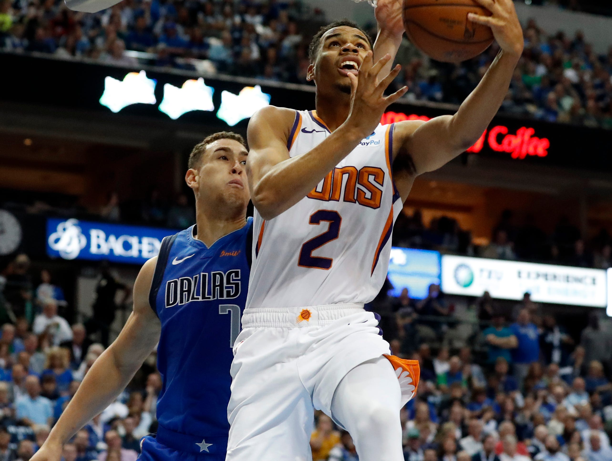 Phoenix Suns guard Elie Okobo (2) gets past Dallas Mavericks forward Dwight Powell (7) for a shot during the first half of an NBA basketball game in Dallas, Tuesday, April 9, 2019. (AP Photo/Tony Gutierrez)