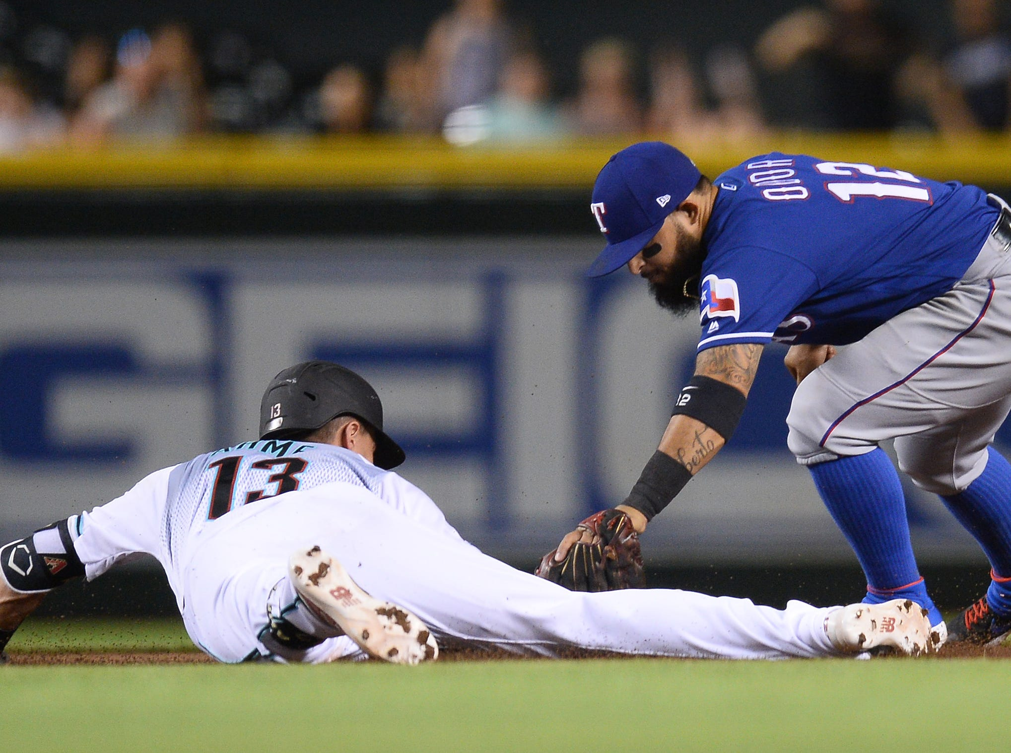 Apr 9, 2019; Phoenix, AZ, USA; Arizona Diamondbacks shortstop Nick Ahmed (13) beats the tag of Texas Rangers second baseman Rougned Odor (12) at second base during the fifth inning at Chase Field. Mandatory Credit: Joe Camporeale-USA TODAY Sports