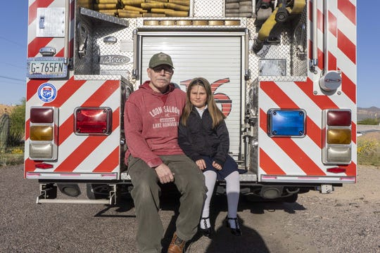 Portrait of Tim Sullivan with his 6-year-old Abi riding in a fire engine #216.