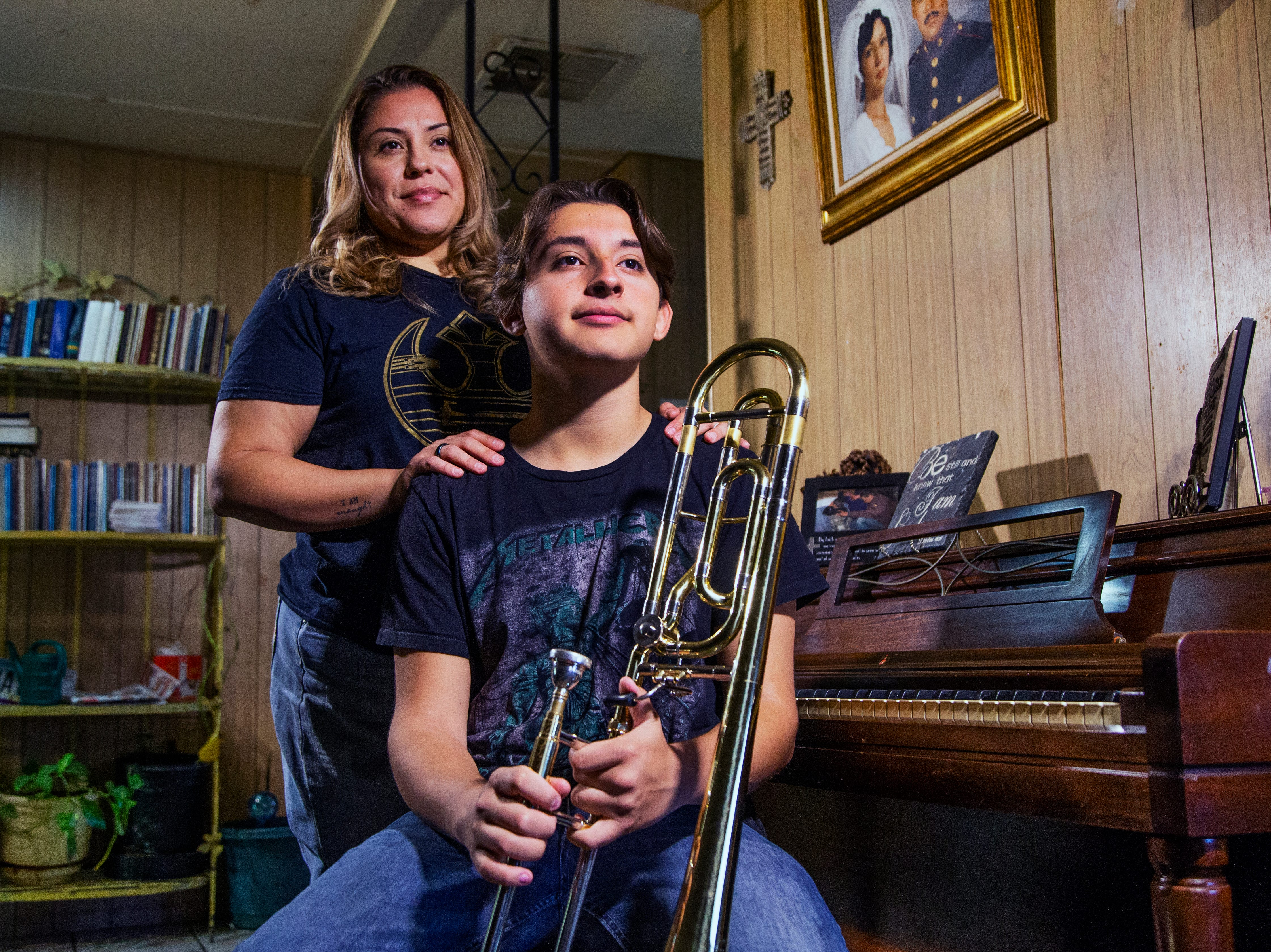 Samuel Osornio, 15, a student at Mesa High School, poses with his trombone and his mom, Dennise Osornio, at home, Feb. 22, 2019. Osornio was suspended from school for throwing a punch at a classmate, who, according to Osornio, was threatening him.