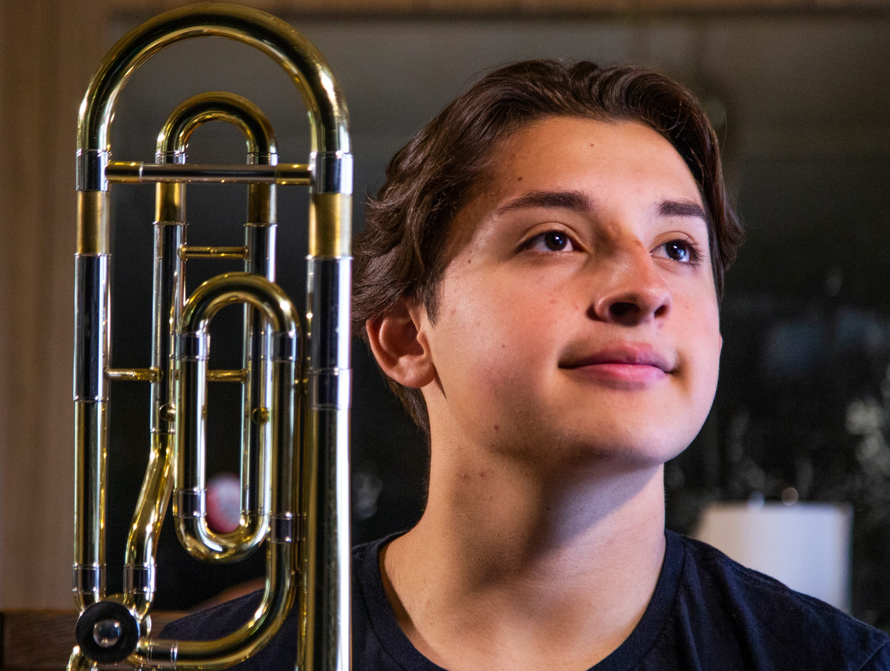 Samuel Osornio, 15, a student at Mesa High School, poses with his trombone at home, Feb. 22, 2019.