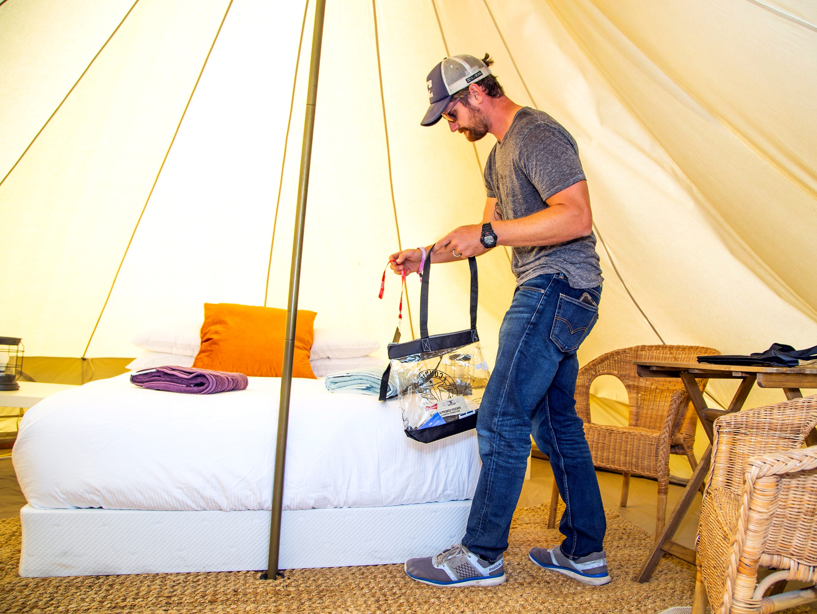 "Josh Langan, owner of Fancy Camps, sets out special towels and other perks inside a tent at the ""glamping"" area at the Country Thunder Arizona 2019 music festival outside Florence April 10, 2019."