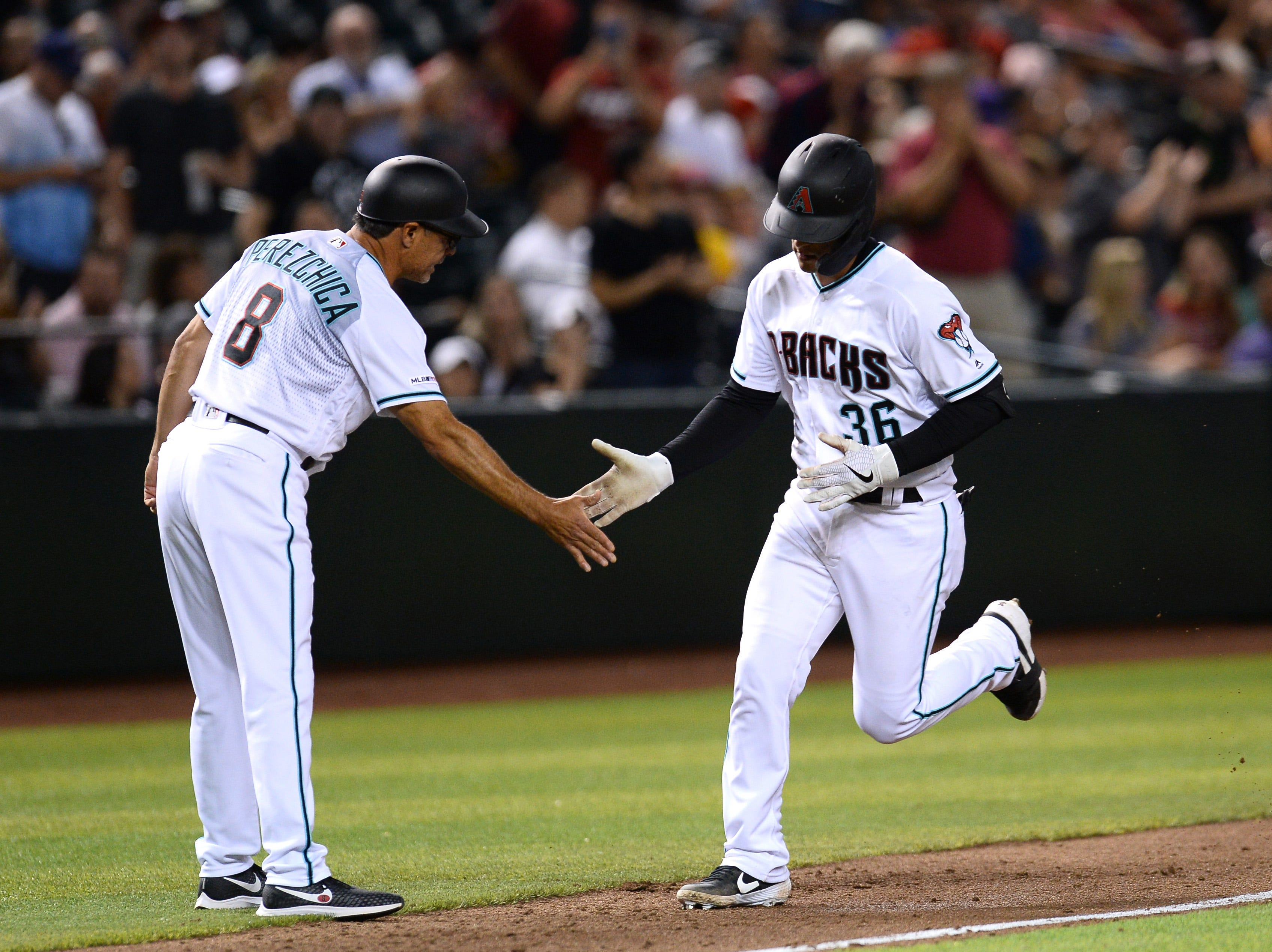 Apr 9, 2019; Phoenix, AZ, USA; Arizona Diamondbacks catcher John Ryan Murphy (36) slaps hands with third base coach Tony Perezchica (8) after hitting a solo home run against the Texas Rangers during the third inning at Chase Field. Mandatory Credit: Joe Camporeale-USA TODAY Sports