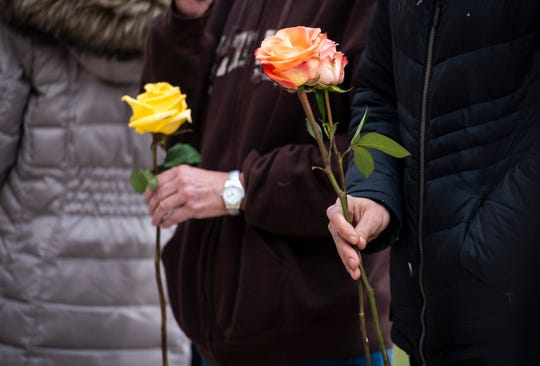 Flowers are handed out before a ceremonial flower toss in honor of National Crime Victims' Rights Week Wednesday, April 10, 2019 outside of the St. Clair County Courthouse in Port Huron.