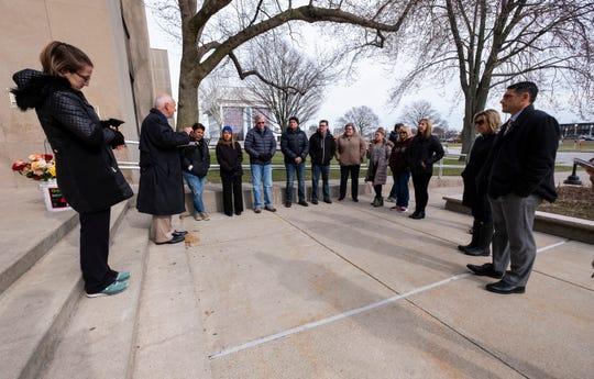 Pastor Tom Seppo, second from left, leads a group gathered for a ceremonial flower toss in prayer Wednesday, April 10, 2019 outside of the St. Clair County Courthouse in Port Huron.