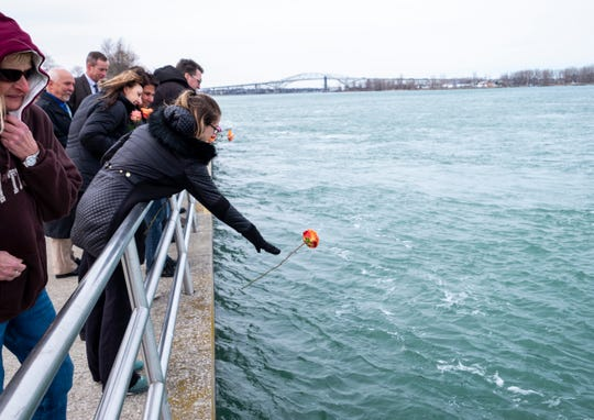 Victims rights advocate Cortney Carl drops a flower into the St. Clair River during a ceremonial flower toss in honor of National Crime Victims' Rights Week Thursday, April 6, 2017 at Kiefer Park in Port Huron.