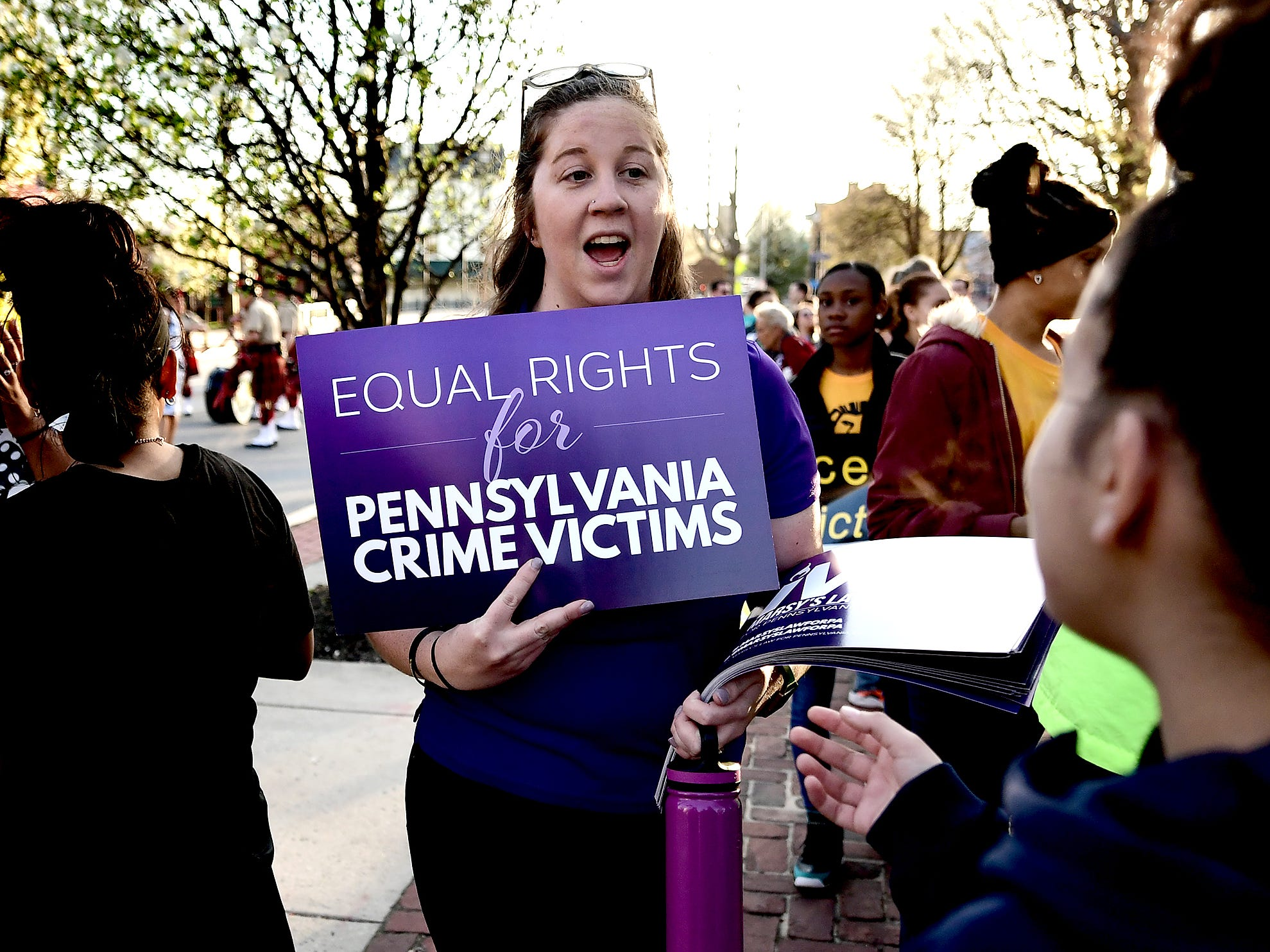 Becca Zelmer, of Marsy's Law for Pennsylvania, passes out signs in support of the bill during a gathering  at the Colonial Courthouse during the 33rd annual Crime Victims' Rights March and Candlelight Vigil Tuesday, April 9, 2019. Participants gathered at the courthouse for a presentation before marching to Trinity United Church of Christ for a ceremony and candlelight vigil. The York County Victims' Rights Coalition sponsored the event. Bill Kalina photo