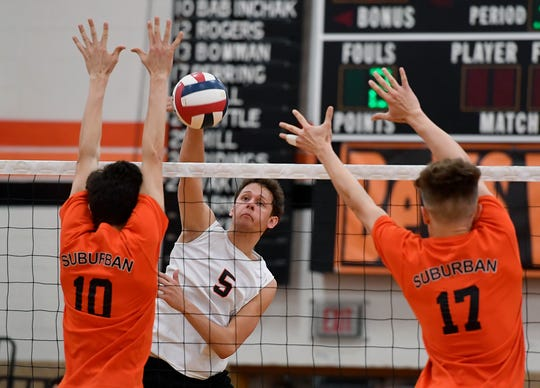 Northeastern's Nate Wolfgang attempts a kill while being blocked by Luke Babinchak, left, and Harrison Perring of York Suburban, Tuesday, April 8, 2019.