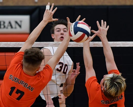 Joel Braswell of Northeastern hammers a kill past Harrison, Perring, left, and Noah Chojnacki of York Suburban, Tuesday, April 8, 2019.John A. Pavoncello photo