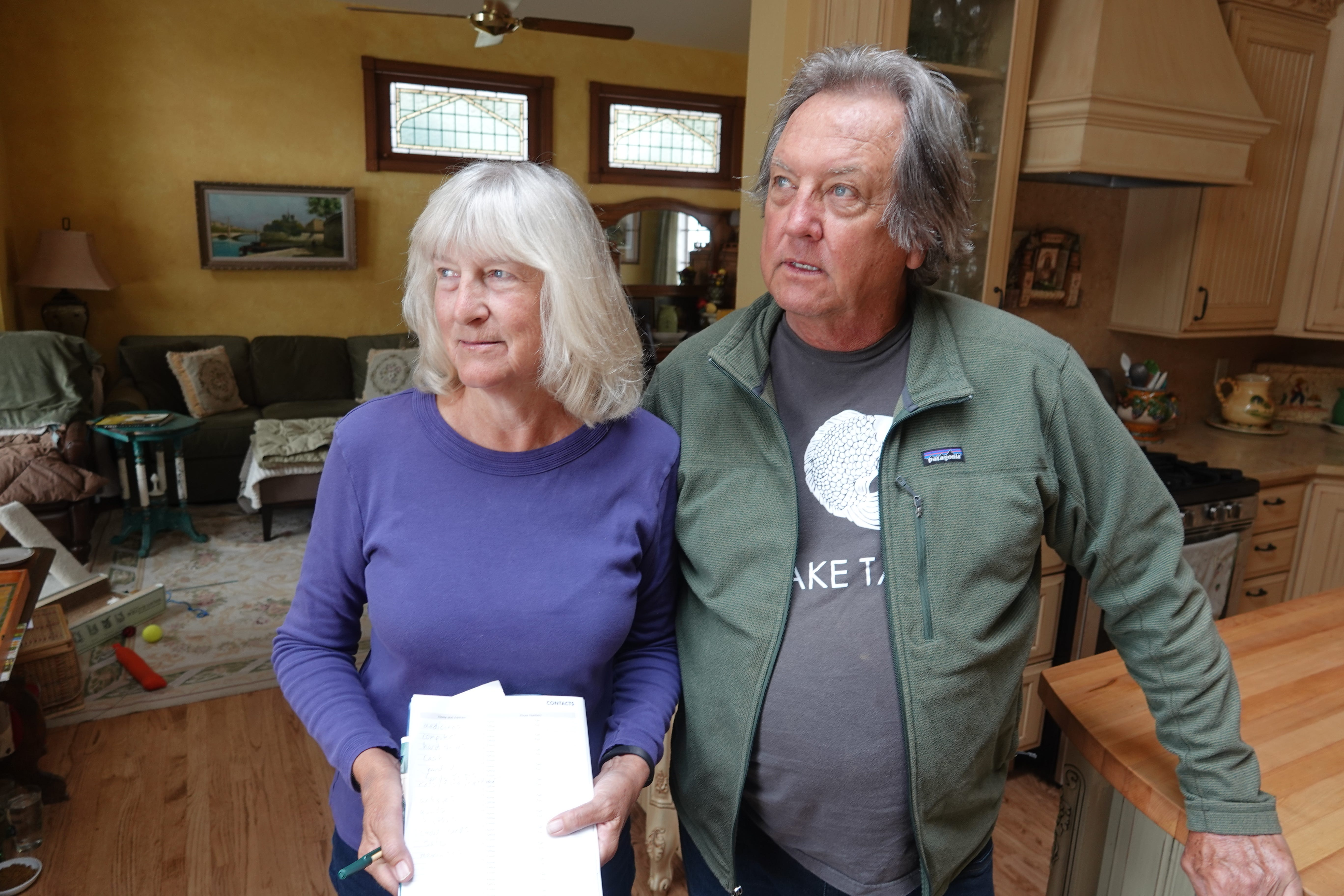 Laura and Ed Heneveld stand in their Olympic Valley, Calif., home with a checklist of items they'd try to save during a wildfire. The couple worries a proposal to add hundreds of homes and nearly 300,000 square feet of commercial development at Squaw Valley Resort could hinder an evacuation.
