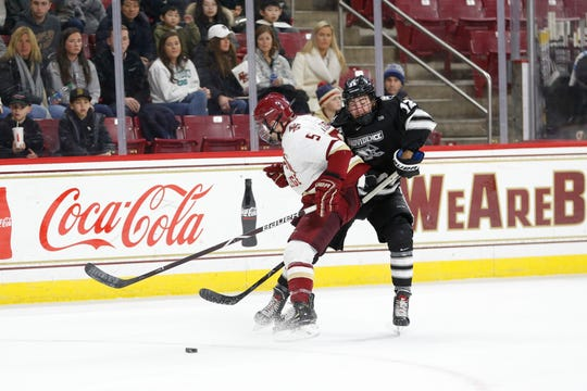 Boston College defenseman Casey Fitzgerald (5) blocks the path Providence College forward Jack Dugan (12) during an NCAA hockey game Jan. 11 in Boston. Dugan has 10 goals, 29 assists and 39 points and is Friars' second-leading scorer as a freshman.