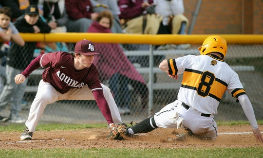 McQuaid's Ben Beauchamp is tagged out by Aquinas third baseman Michael Altpeter trying to steal the base.
