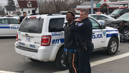 The driver of an allegedly stolen vehicle that drew police on a high-speed chase through Rochester is escorted in handcuffs to a police cruiser after the vehicle crashed at Buffalo and Howard roads on Wednesday, April 10, 2019.