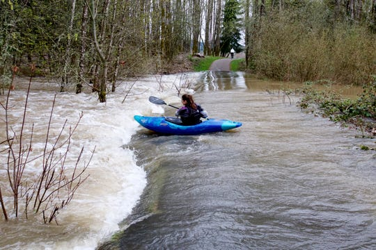 Priscilla Macy kayaks over a small rapid caused by a flooded trail at Minto-Brown Island Park as the Willamette River rose to 25 feet — its highest level since 2012.