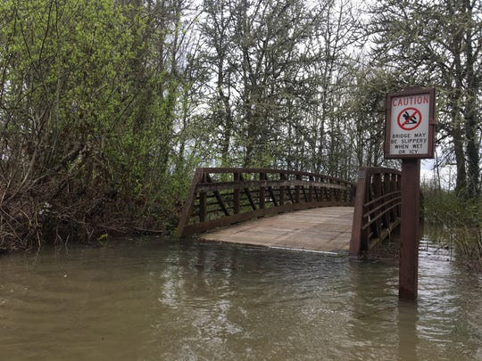 Flood waters rise to a bridge in Minto-Brown Island Park Wednesday, April 10, 2019.