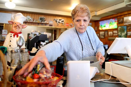 Owner Marlene Blanchard refills the candy bowl on the counter at the Court Street Dairy Lunch in downtown Salem on April 10, 2019. The old-fashioned diner opened in 1929 and is the city's oldest restaurant.