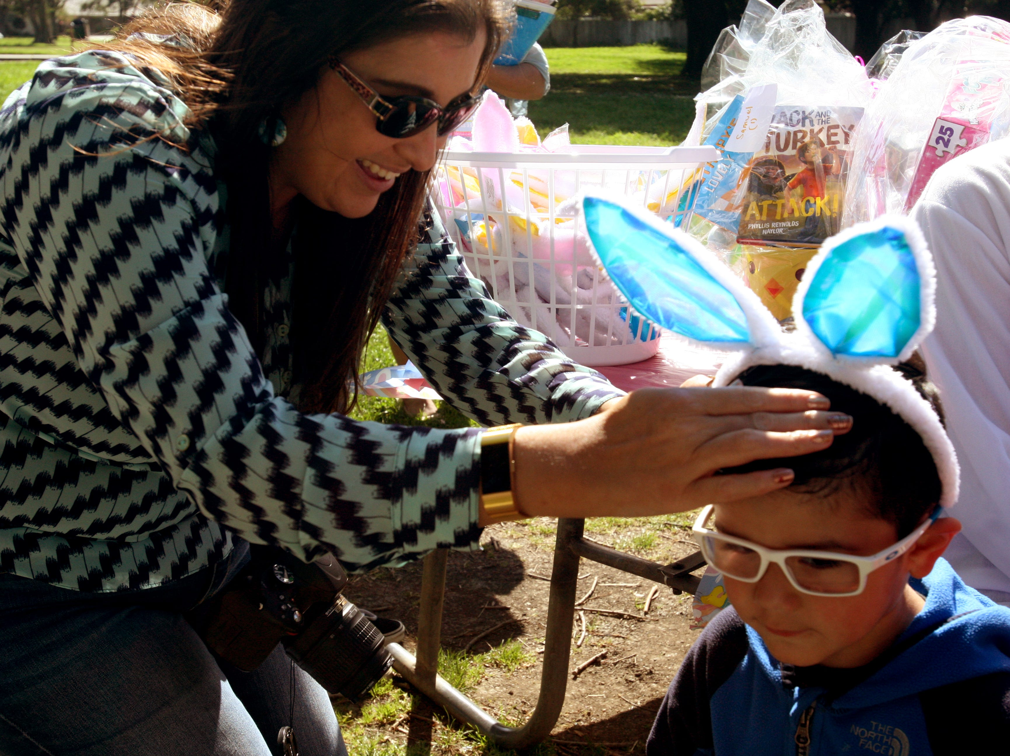 Maverick Rodriguez, 2, gets his bunny ears straightened out by a volunteer with Partnership for Children. April 9, 2019