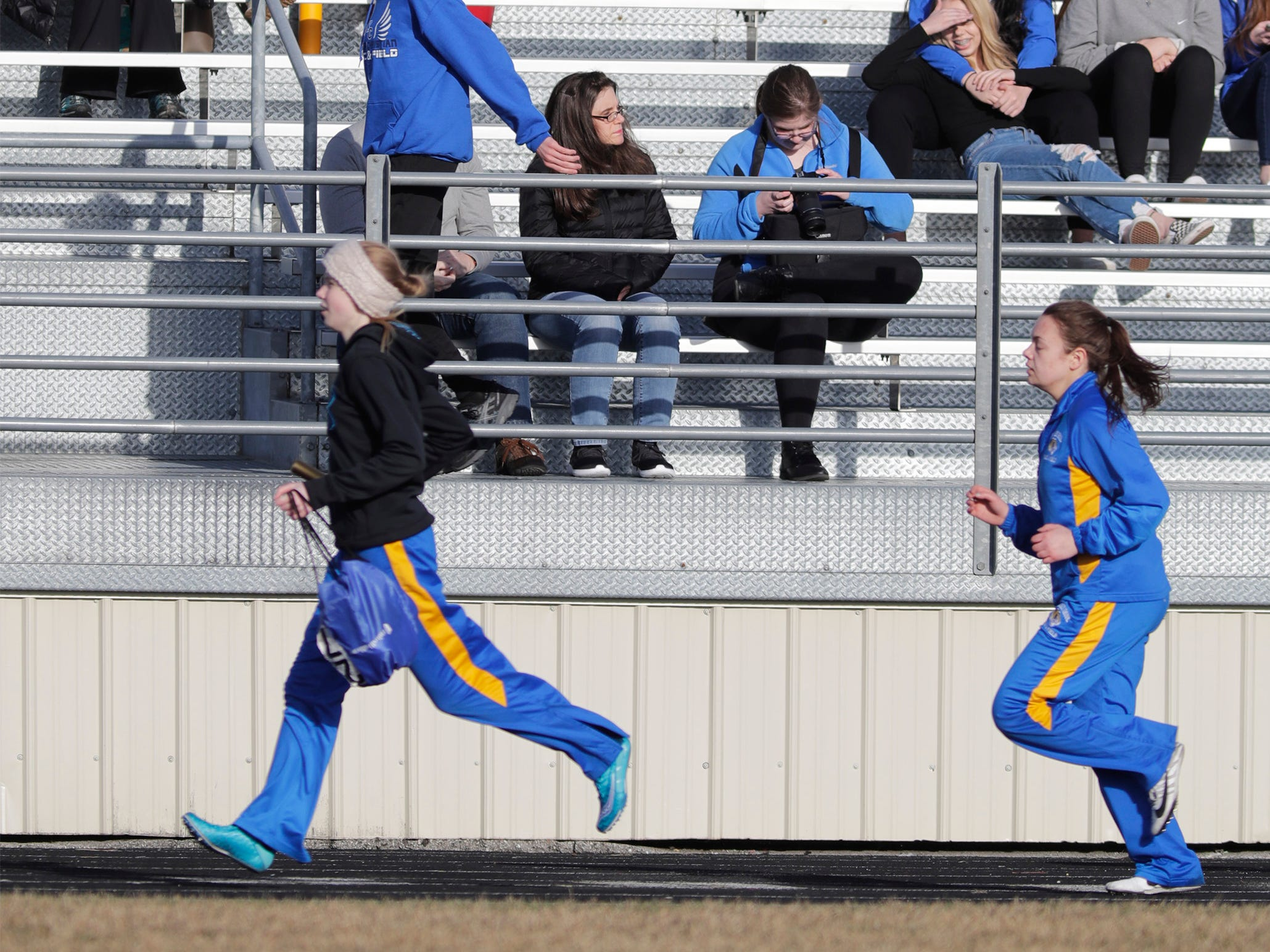 Track spectators watch action on the track at the Howards Grove track meet, Tuesday, April 9, 2019, in Howards, Wis.