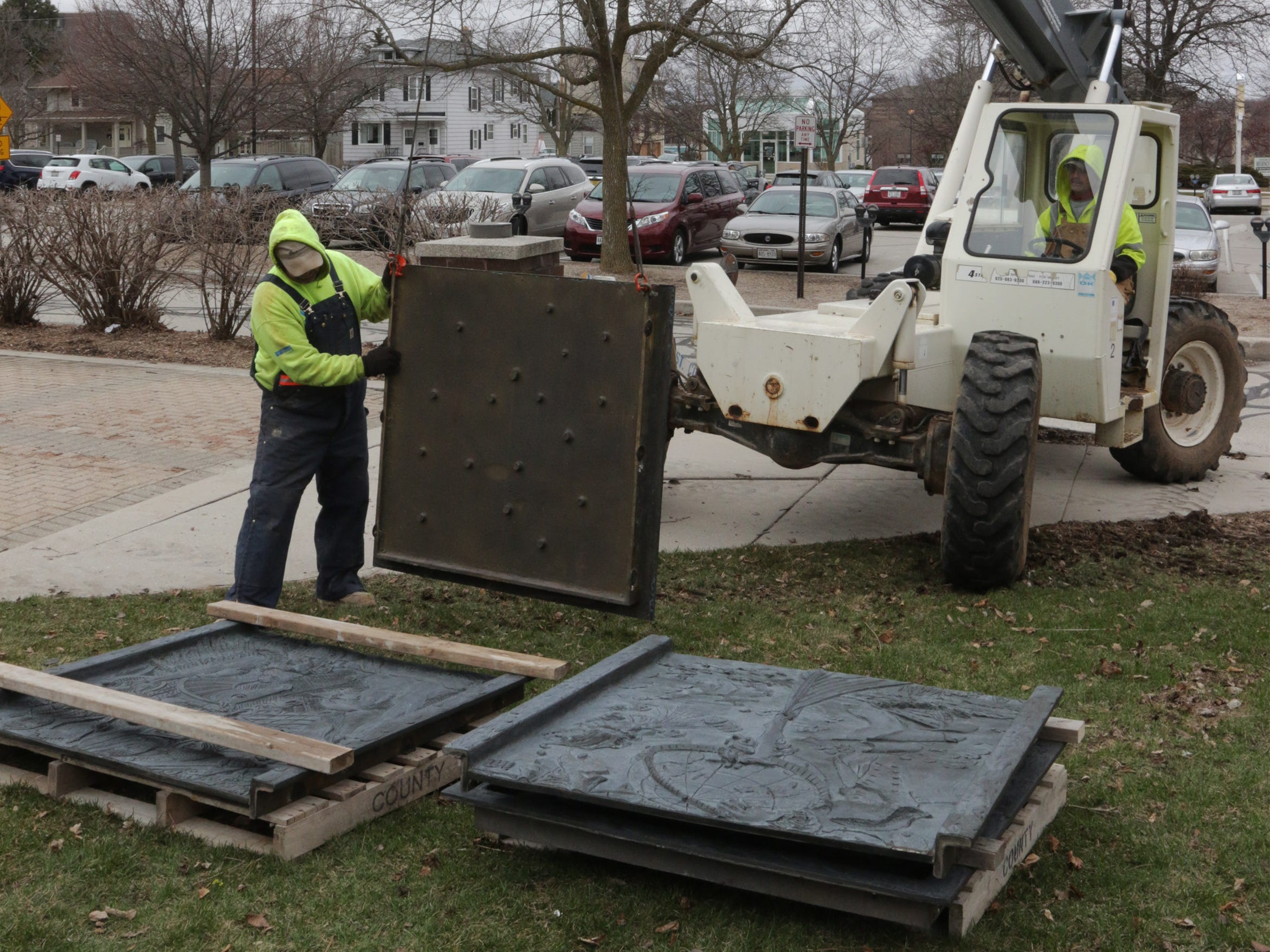 Employees from Koenig Constructions lower the 800-pound cast panels from the clock tower at Mead Public Library, Wednesday April 10, 2019, in Sheboygan, Wis. The city is repurposing the cast panels for an 8th Street display as part of a renovations project.