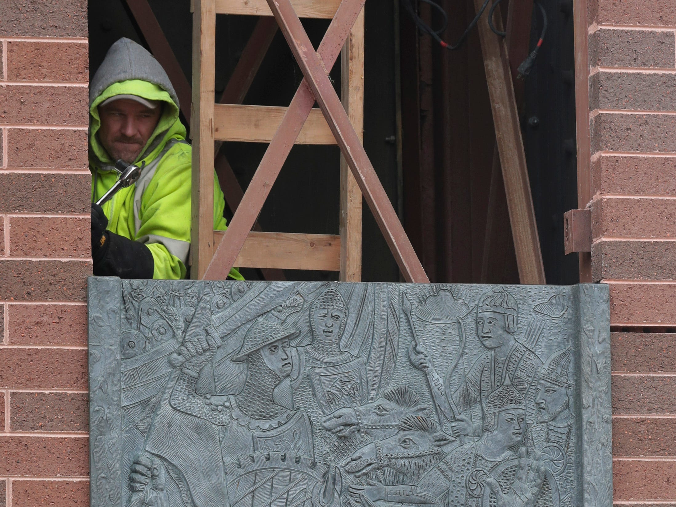 An employee from Koenig Constructions works to unbolt brass panels from the clock tower at Mead Public Library, Wednesday April 10, 2019, in Sheboygan, Wis. The city is repurposing the cast panels for an 8th Street display as part of a renovations project.