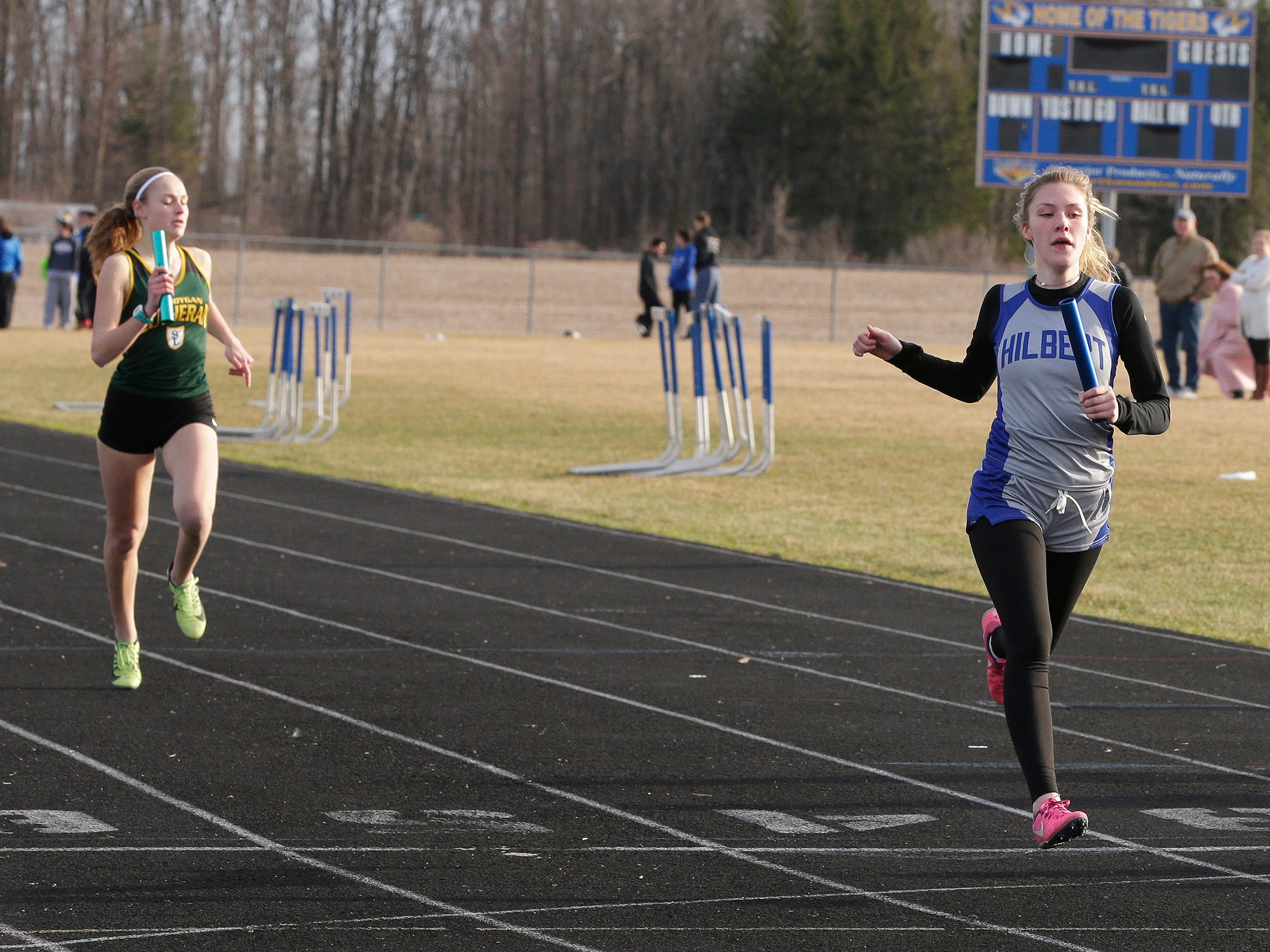 Courtney Gehl, right, crosses the finish line during the 4 X 200 at the Howards Grove track meet, Tuesday, April 9, 2019, in Howards, Wis.