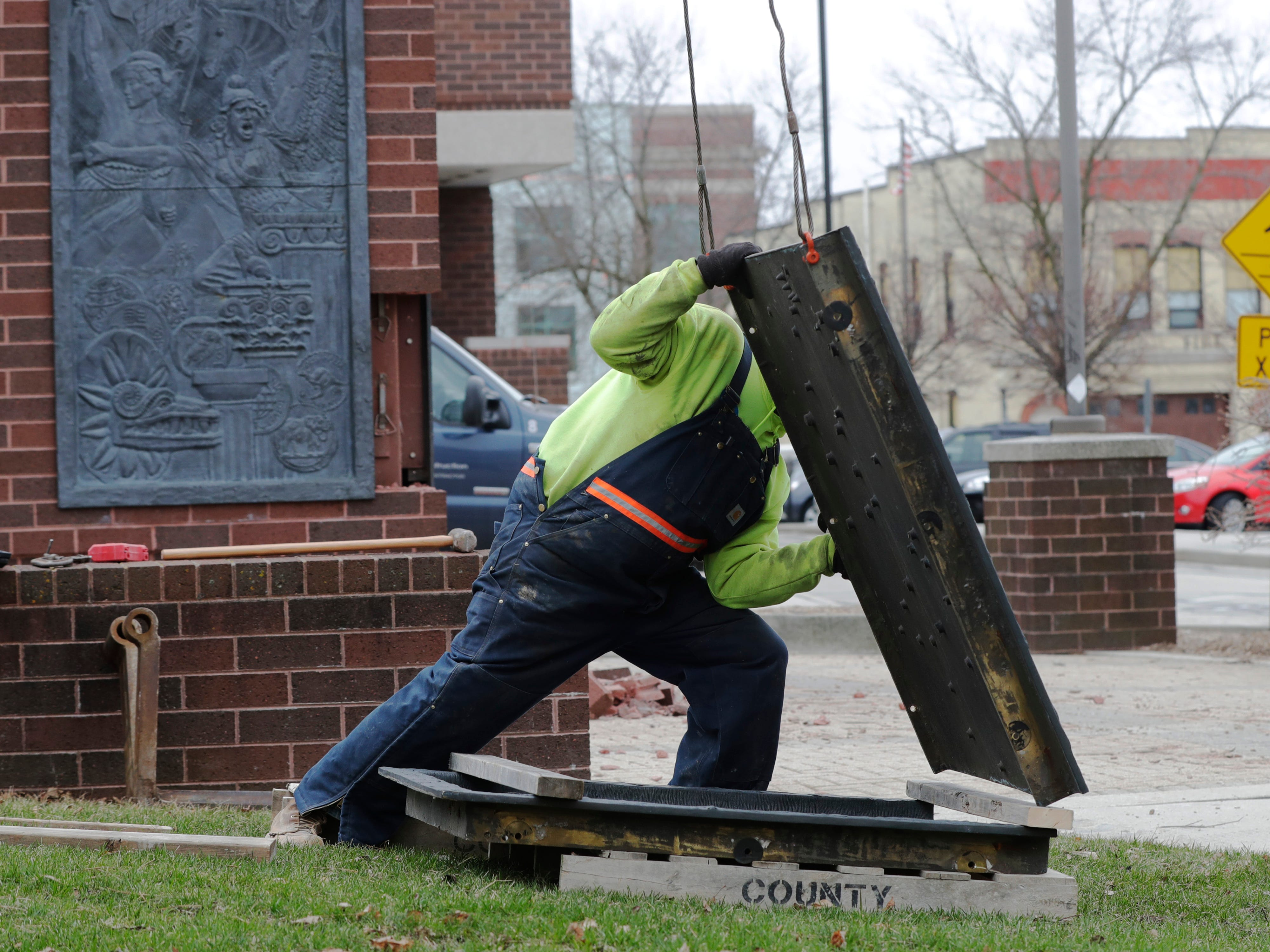 An employee from Koenig Construction steadies the bronze panel from the clock tower at Mead Public Library, Wednesday, April 10, 2019, in Sheboygan, Wis.