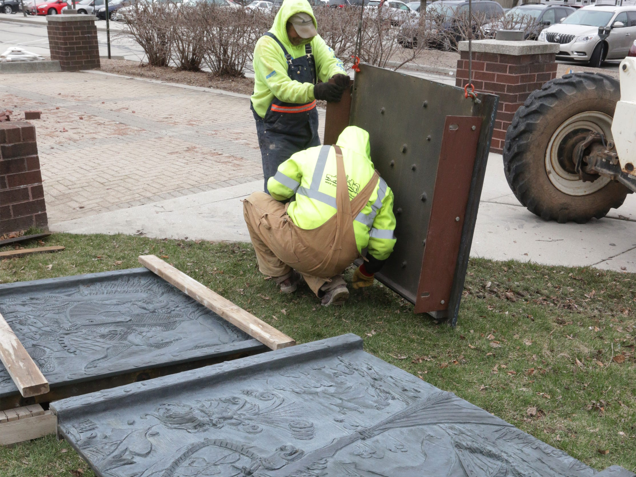 Employees from Koenig Constructions secure the 800-pound cast panels from the clock tower at Mead Public Library, Wednesday April 10, 2019, in Sheboygan, Wis. The city is repurposing the cast panels for an 8th Street display as part of a renovations project.