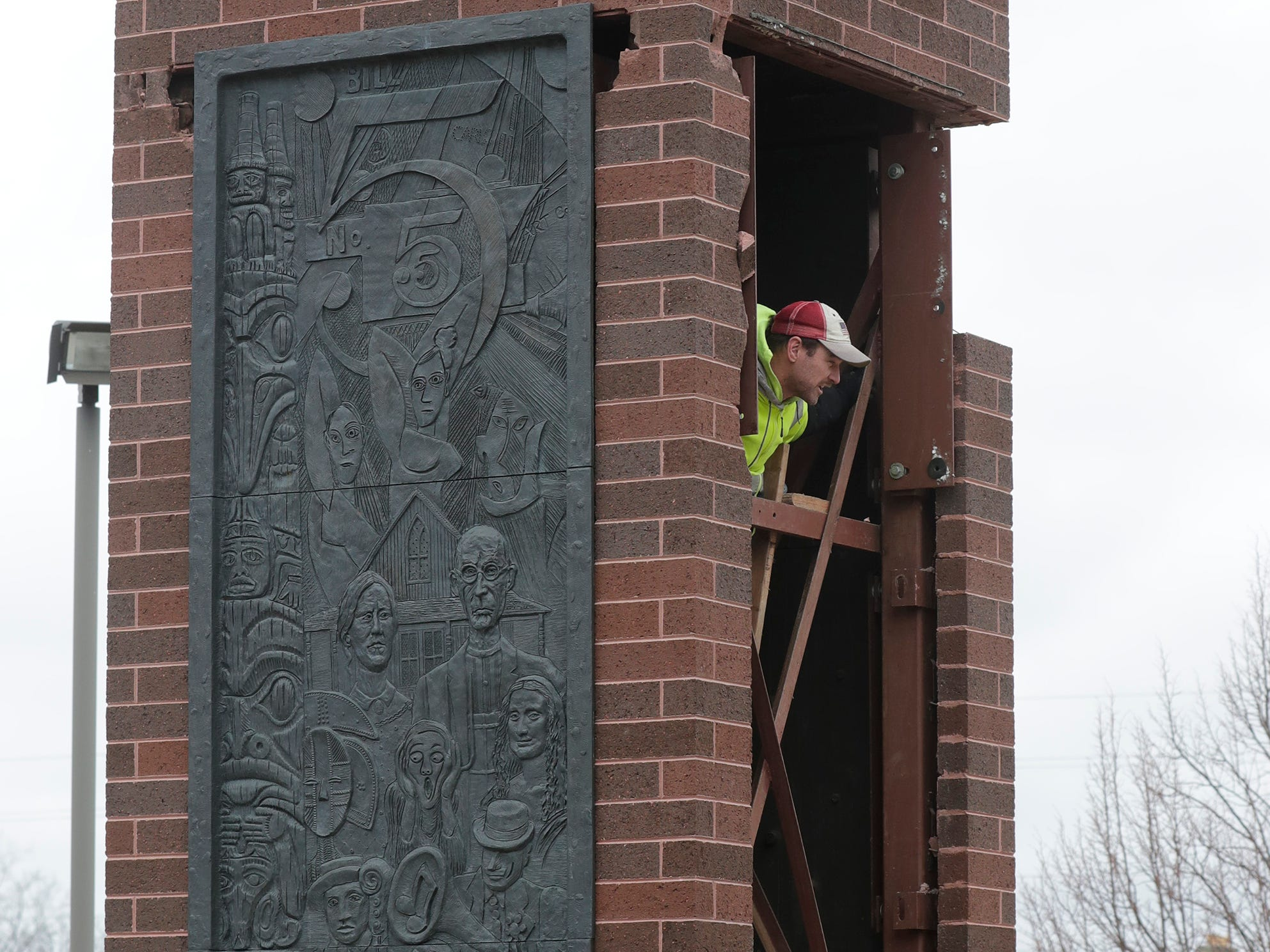An employee from Koenig Constructions peers out from inside the clock tower at Mead Public Library, Wednesday April 10, 2019, in Sheboygan, Wis. The city is repurposing the cast panels for an 8th Street display as part of a renovations project.